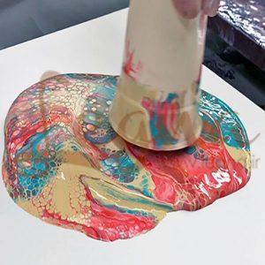 رنگهای رزینی که روی هم در یک لیوان ریخته شده و یکجا برگردانده میشوند روی سطح کار برای اجرای یک اثر فلوید آرت